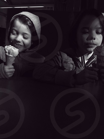 two children eating ice cream on table gray scale photography  photo