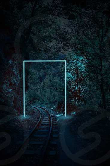 Creative night landscape of rails in the forest layout with neon frame. Supernatural concept. Ultra blue colors. photo