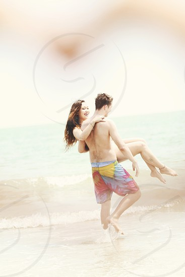 Couple laughing having fun on the beach  photo