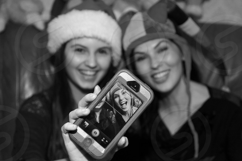 grayscale photography of women wearing clown cap taking a picture together photo