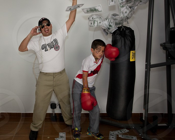 man and boy next to everlast black boxing bag boy resting in boxing gloves photo
