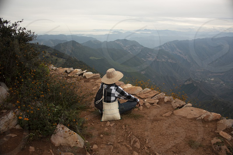 Woman meditating on the mountain while in the background in the distance the fog begins to climb between the rocks photo