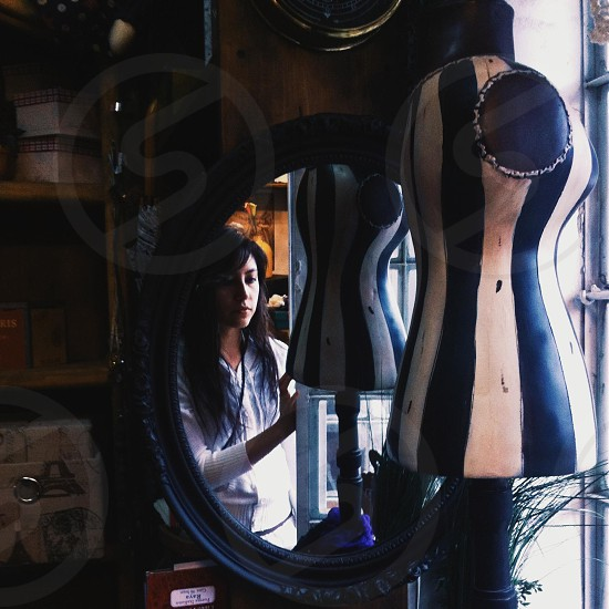 woman reflected on oval mirror photo