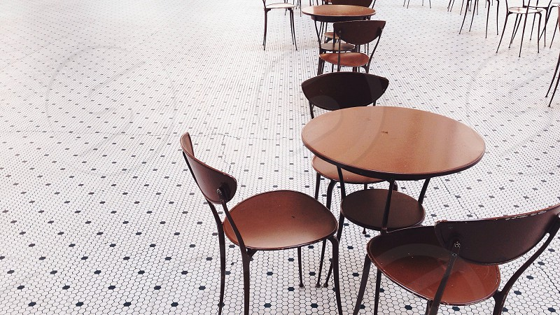 brown wooden table and chairs on white and black floor photo