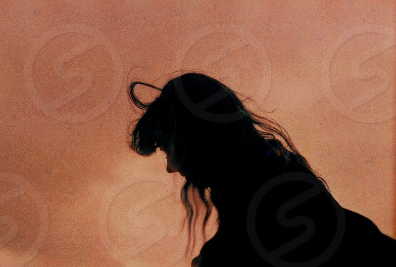 silhouette of person with long hair during dusk photo