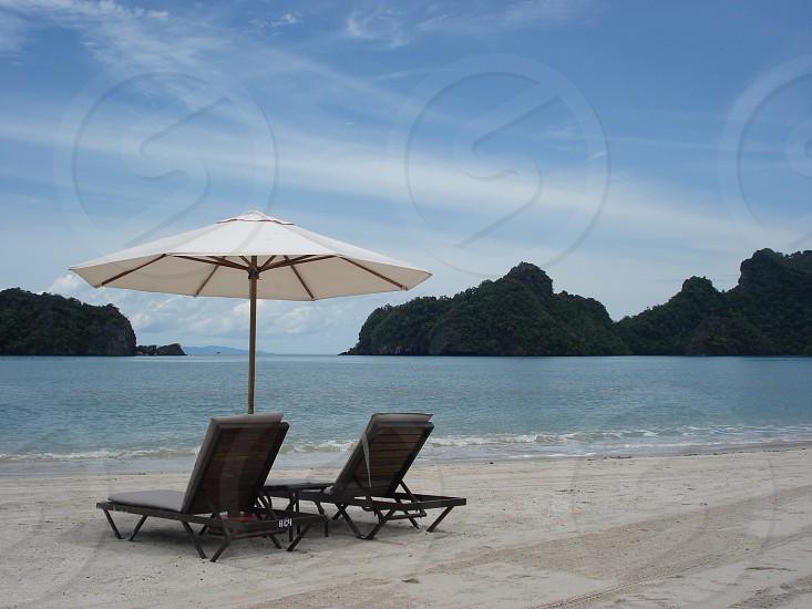 brown wooden beach lounge with white beach umbrella on white sand beach photo