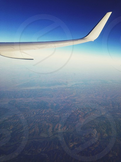white airplane wing outside plane window photo
