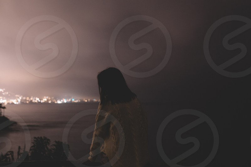 woman in beige sweater neat the sea under grey cloudy sky photo
