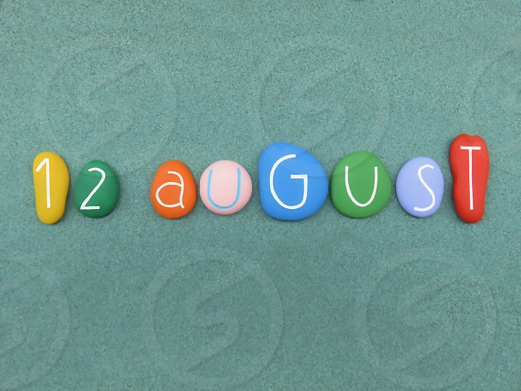 12 August calendar date composed with multi colored stones over green sand                                photo