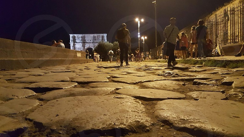 group of people walking down gray pavement with street lamps during night time photo