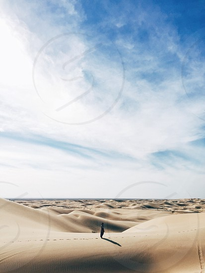 woman in white t shirt standing on desert during daytime photo