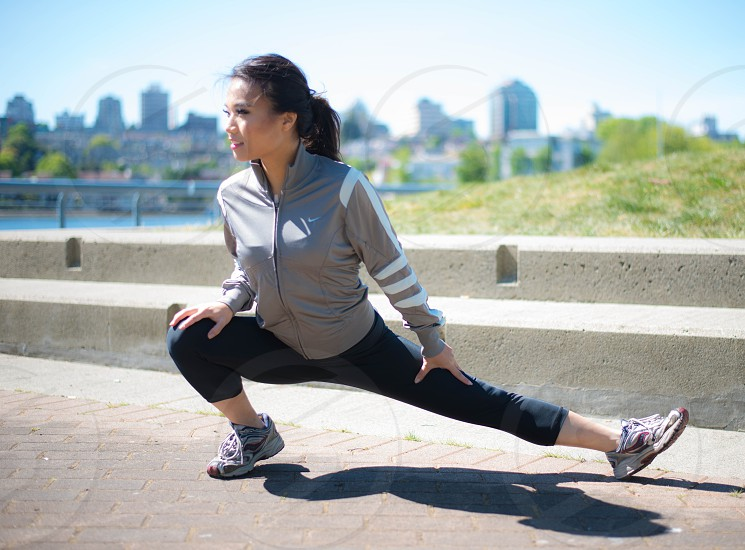 woman in gray jacket and black pants wearing running shoes stretching on gray concrete pavement during daytime photo