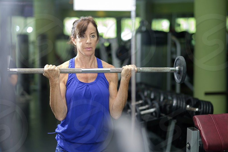 Retired senior woman working out with weight handle bar in front of mirror at the gym photo