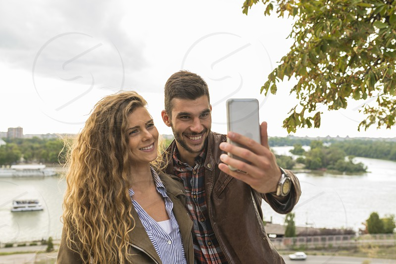 Happy and young attractive lovers enjoying the time near the river bank by taking a selfie photos photo