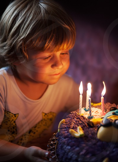 Little boy blows out candles in the cake for his 4th birthday photo