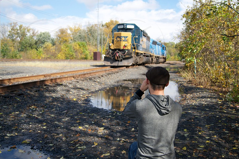 man with short brown hair in newsboy cap and gray hoodie taking picture of train heading in his direction on tracks photo