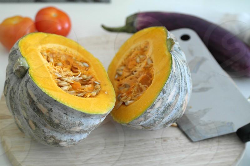 sliced green squash near knife on round cutting board near eggplant and tomatoes photo
