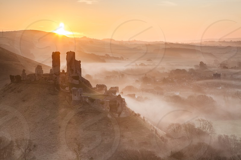 Corfe castle Dorset England historical location sunrise mist fog landscape. photo
