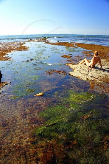 woman in string bikini on rock in pond photo