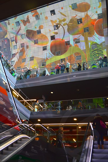 people inside a mall with escalators and glass roof photo