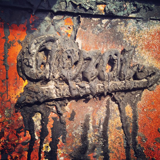 Years of tar and decay cover this emblem  photo