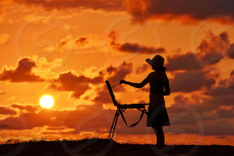 silhouettes of woman wearing hat and dress painting at sunset photo