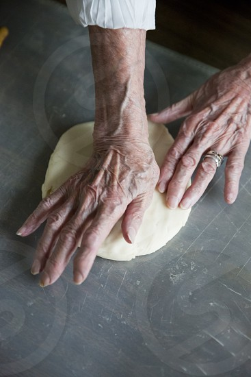 An elderly woman preparing a pie crust photo