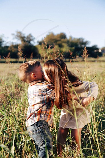 gril in white dress in grassy field kissing boy in plaid shirt and blue jeans photo