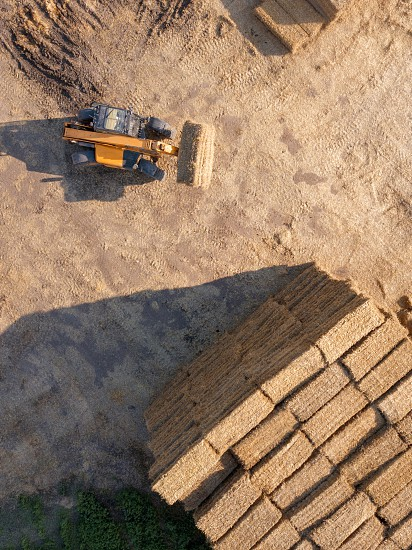 Aerial view of a tractor folding bales of hay in a field on a sunny autumn day. Photo from drone. Top view photo