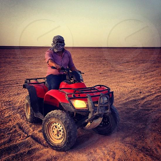 man riding red atv photo