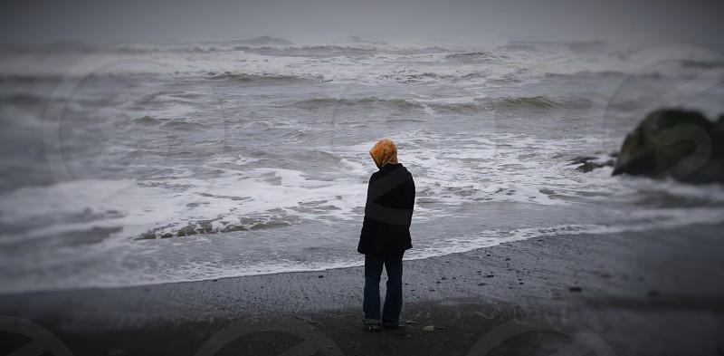 woman in black coat standing on seashore photo