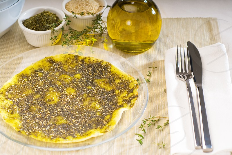 lebanese manouche or manoushe lebanese pizza with thyme and sesame seedszaatar and extra virgin olive oil on top photo
