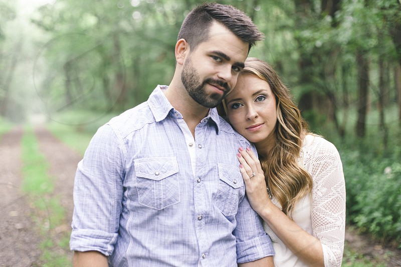 couple standing side by side on dirt trail lined with trees photo