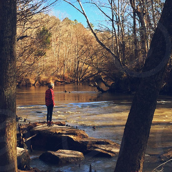 image of woman wearing red dress shirt standing on boulder beside river during daytime photo