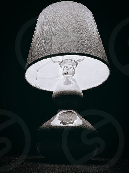 low angle photo of gray ceramic base and gray top table lamp in dark room photo