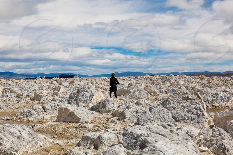 person standing on white jagged rocks photo