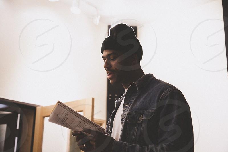man in black bonnet holding notepad photo