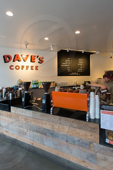 man in brown shirt and black red cap standing near dave's coffee signage photo