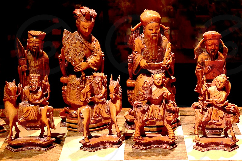 Detail of antique Chinese hand-carved wooden chess figures photo