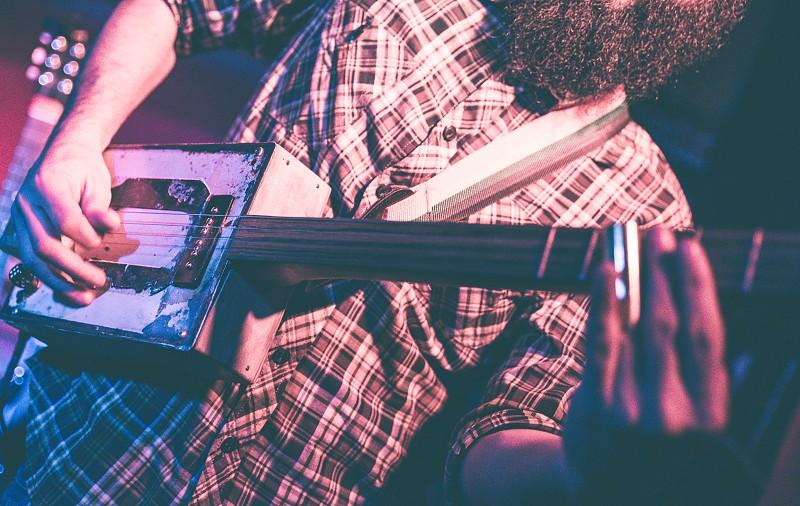 Musician playing a strange rectangular guitar built by himself photo