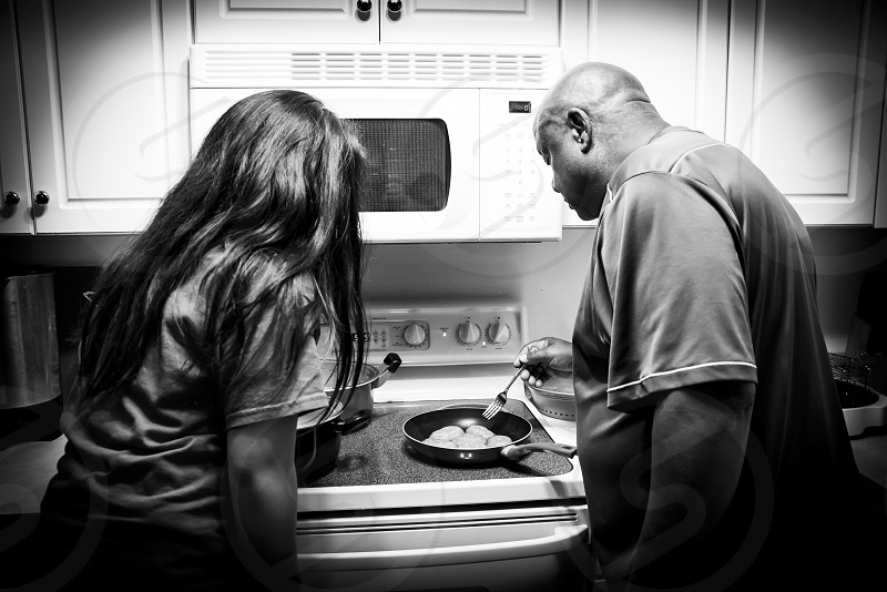 Grandfather showing granddaughter how to cook. photo
