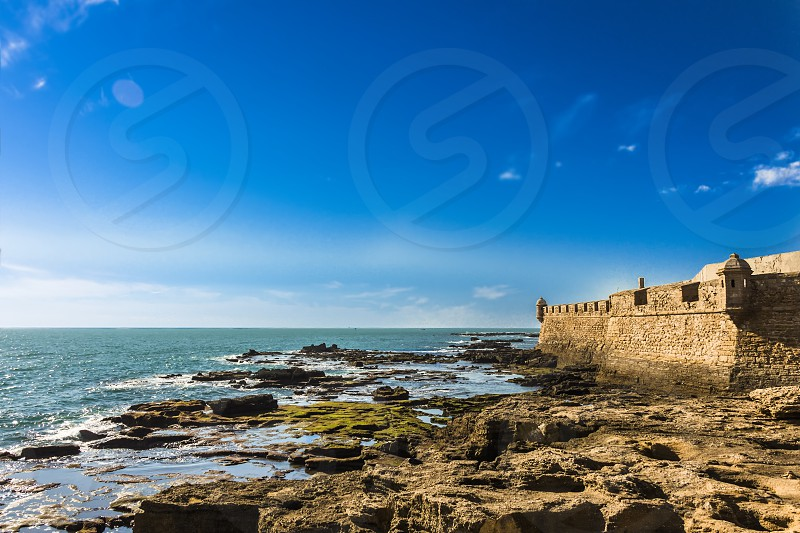 Moss covered rocks off the coastline of Castillo de San Sebastian in Cadiz photo