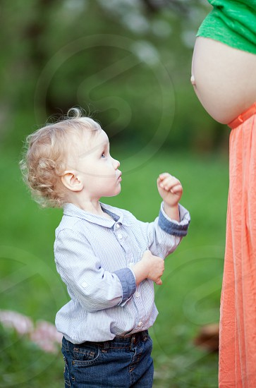 Lovely little boy looking at pregnant mothers belly outdoor. He is expecting to have brother or sister photo