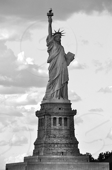 grayscale photo of statue of liberty below cloudy sky during daytime photo