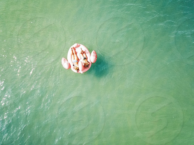 Minimalist water ocean float summer girls women fun sea waves play wet bikini floating minimal aerial drone travel active adventure explore photo