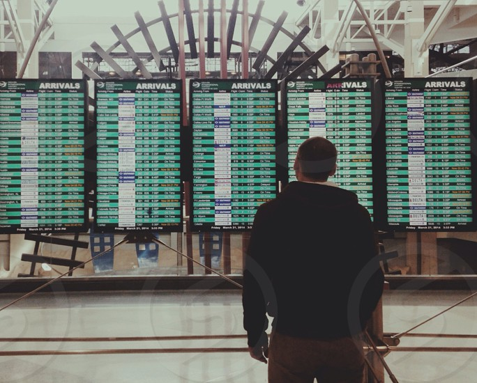 man in black hoodie and khakis looking at arrivals board in airport photo