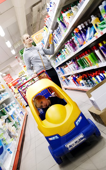 Mother and son shopping in a supermarket with the little boy riding in a colourful plastic toy car attached to the shopping trolley photo