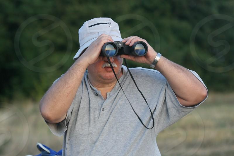 man in grey henley t shirt using binoculars photo