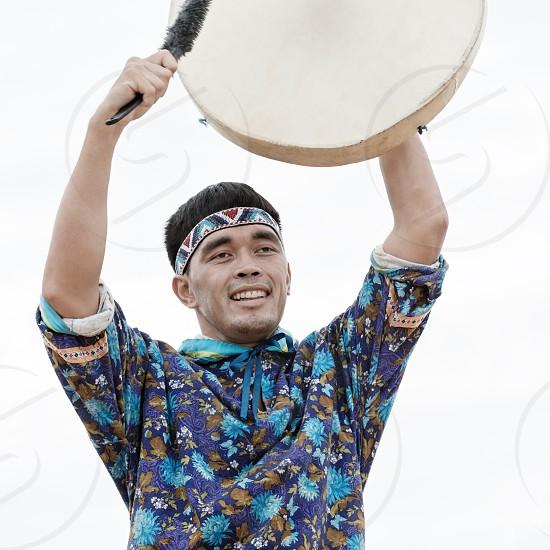 KAMCHATKA PENINSULA RUSSIA - AUGUST 9 2014: Emotional man dancer dancing with a tambourine. Public concert Koryak Folk Dance Ensemble Angt on the Khalaktyrsky Beach around the City Petropavlovsk-Kamchatsky. photo