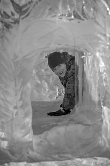 toddler crawling inside ice cave photo